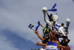 Demonstrators fly Nicaragua flags atop the Alexis Arguello monument during a march against Nicaragua's President Daniel Ortega in Managua, Nicaragua, Wednesday, May 30, 2018. Violence returned to protests against Nicaraguan President Daniel Ortega's government when riot police and government supporters confronted protesters during a mothers day march to commemorate those mothers who has lost their children during the ongoing protests.(AP Photo/Alfredo Zuniga)